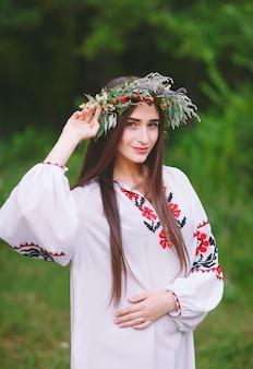Ein junges mädchen von slawischem aussehen mit einem kranz aus wilden blumen im hochsommer.