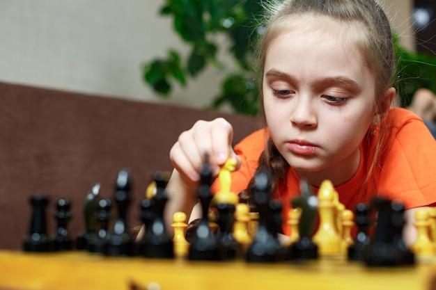 Ein junges mädchen während der quarantäne spielt zu hause schach auf dem sofa liegend.