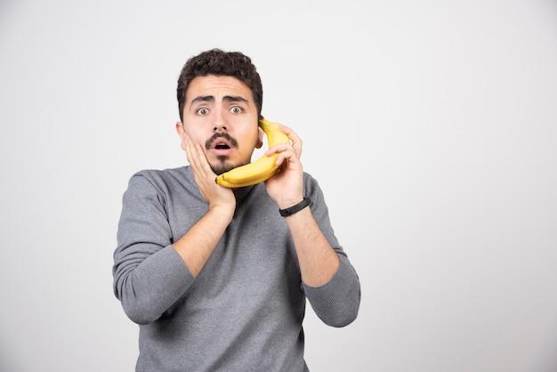 Ein junges mannmodell, das eine banane als telefon hält.