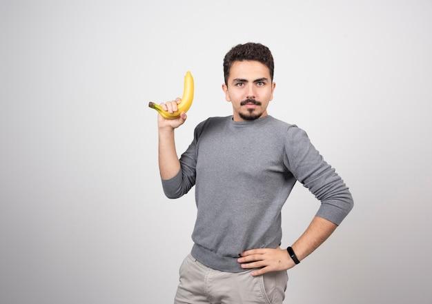 Ein junges mannmodell, das eine banane hält.