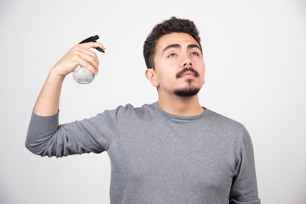Ein junges mannmodell, das plastiksprühflasche hält.