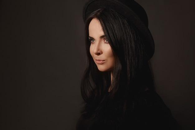 Ein junges model-mädchen mit sanftem make-up und perfekten schwarzen haaren in einem trendigen schwarzen hut posiert auf dem...