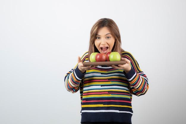 Ein junges niedliches frauenmodell, das eine hölzerne platte mit bunten frischen äpfeln hält.
