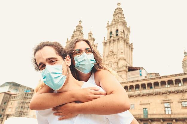 Ein junges paar, das auf reisen eine gute zeit hat und die masken aufgesetzt hat