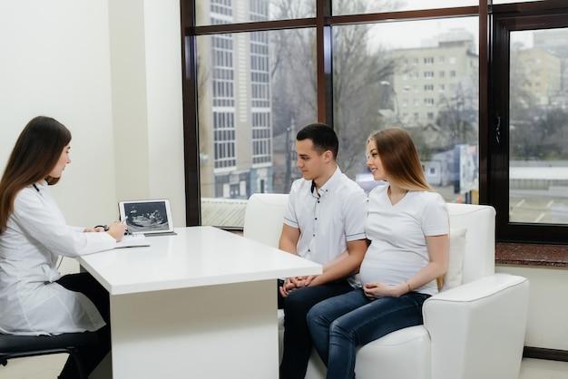 Ein junges paar, das darauf wartet, dass ein baby nach einem ultraschall einen frauenarzt konsultiert. schwangerschaft und gesundheitsversorgung