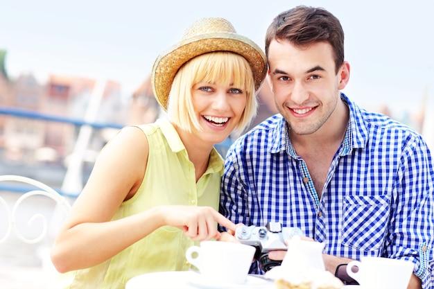 Ein junges paar, das im café seine kamera überprüft