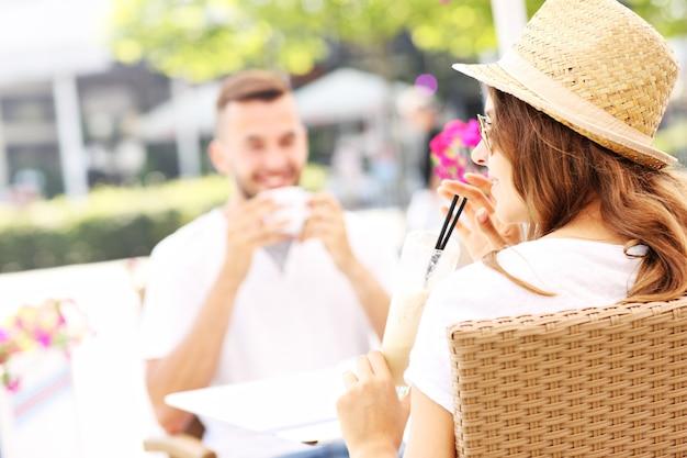 Ein junges paar, das im sommer im café sitzt