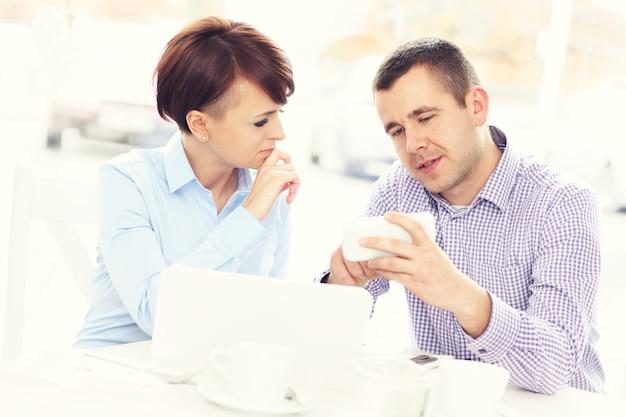 Ein junges paar, das in einem restaurant an einem laptop arbeitet