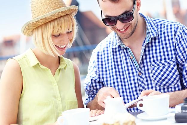 Ein junges paar, das in einem restaurant einen reiseführer liest