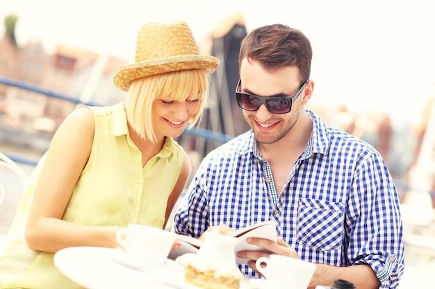 Ein junges paar, das in einem straßencafé einen reiseführer liest