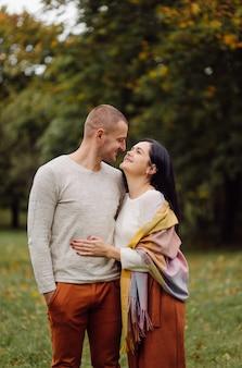 Ein junges paar, das spaß im herbstpark hat. dating, attraktiv