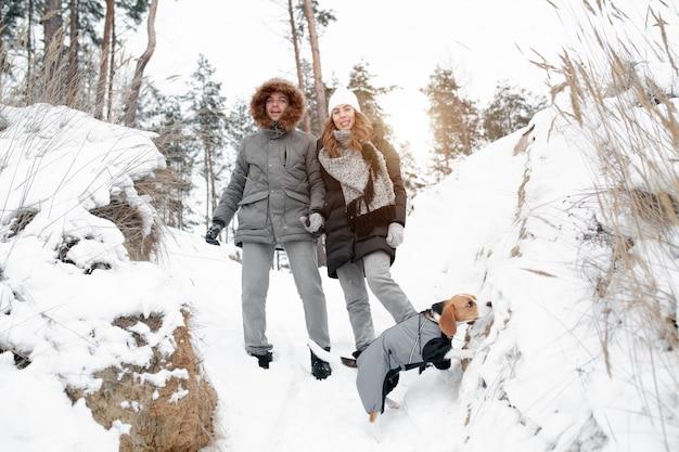 Ein junges paar, ein mann und eine frau gehen mit ihrem hund spazieren
