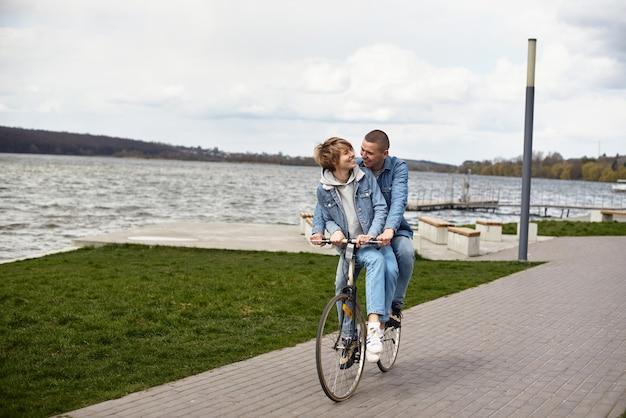 Ein junges paar fährt mit dem fahrrad am see entlang.
