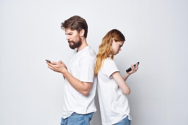 Ein junges paar in weißen t-shirts mit telefonen in den händen isolierter hintergrund. foto in hoher qualität