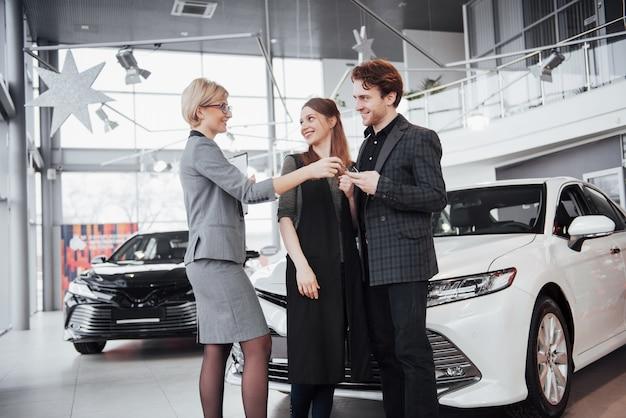 Ein junges paar kauft ein neues auto. diller gibt ihnen kay