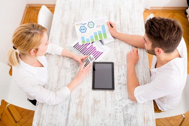 Ein junges paar organisiert ihre finanzielle situation zu hause.