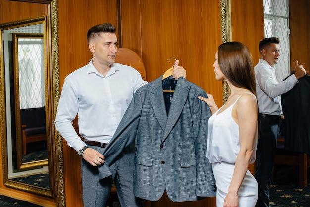 Ein junges paar probiert neue kleider in der umkleidekabine eines ladens an, der in einem supermarkt einkauft
