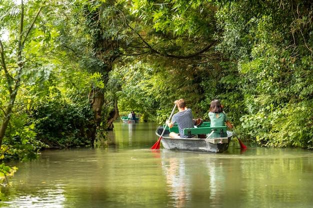 Ein junges paar rudert das boot segeln zwischen la garette und coulon, marais poitevin das grüne venedig, in der nähe der stadt niort, france