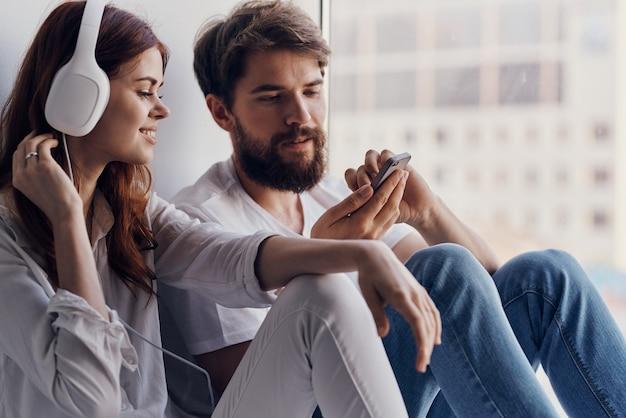 Ein junges paar sitzt am fenster mit kopfhörern zusammen wohnungen technik