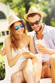 Ein junges paar sitzt auf einer bank mit smartphones
