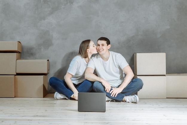 Ein junges paar sitzt mit einem laptop in der wohnung.