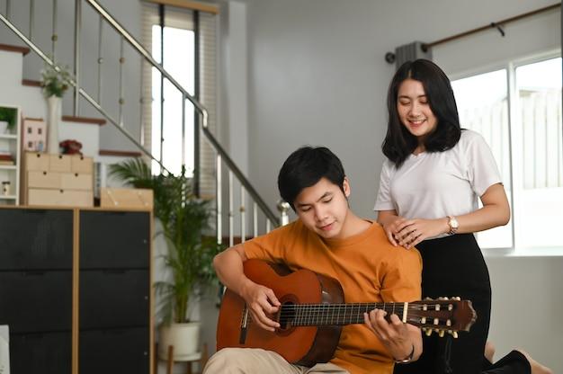 Ein junges paar spielt zusammen gitarre auf der couch im wohnzimmer zu hause