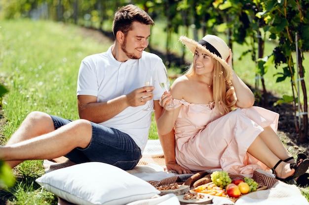 Ein junges paar teilt einen glücklichen moment, der auf dem gras in der landschaft picknickt