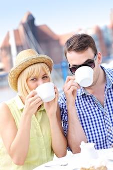 Ein junges paar trinkt kaffee in einem café im freien in der danziger marina
