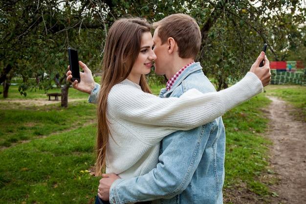 Ein junges paar verbringt zeit miteinander im park, umarmt sich und schaut auf seine handys. kerl mit einem mädchen mit gadgets im park