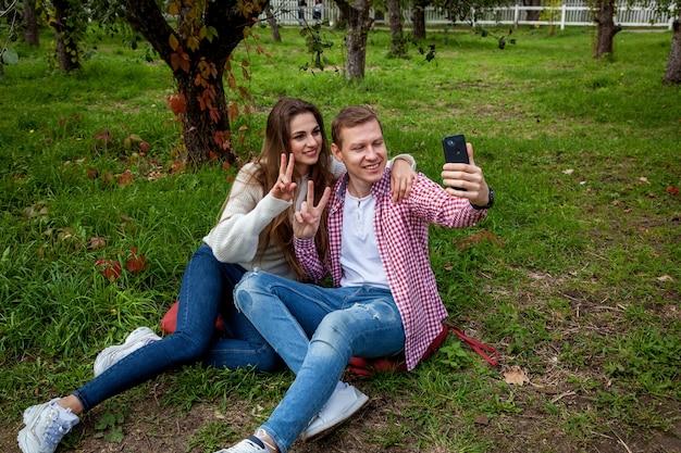 Ein junges paar verbringt zeit zusammen im park, sitzt im gras und macht selfies am telefon. der typ mit einem mädchen mit gadgets im park