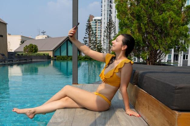 Ein junges schlankes mädchen verbringt zeit am telefon und entspannt sich am pool.