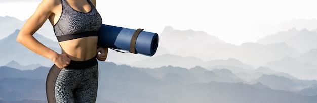 Ein junges, schlankes, sportliches mädchen in sportbekleidung führt eine reihe von übungen vor dem hintergrund der berge durch