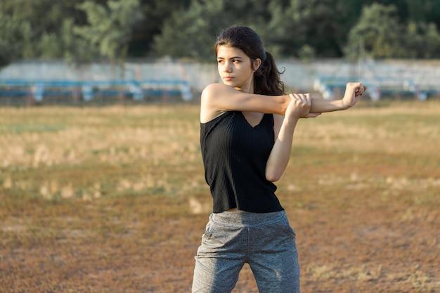 Ein junges schlankes sportliches mädchen in sportbekleidung mit schlangenhautdrucken führt eine reihe von übungen durch. fitness und gesunder lebensstil.