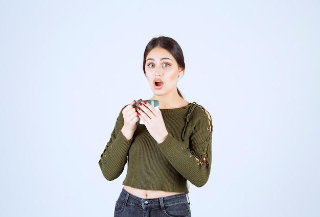 Ein junges schockiertes frauenmodell, das eine tasse hält und die kamera betrachtet.
