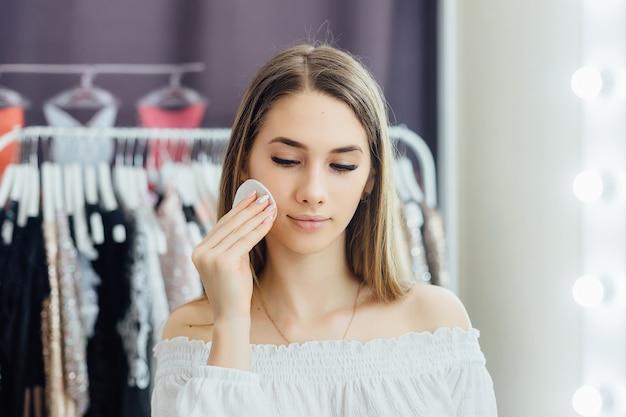 Ein junges schönes blondes mädchen macht ihr eigenes make-up vor dem spiegel
