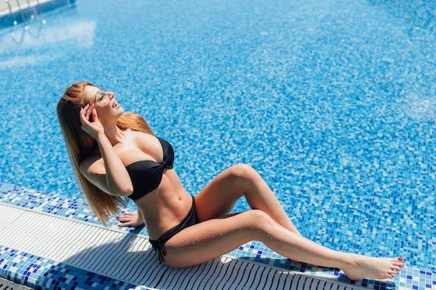 Ein junges schönes braunhaariges mädchen mit großen titten in einem schwarzen badeanzug, sonnenbrille,