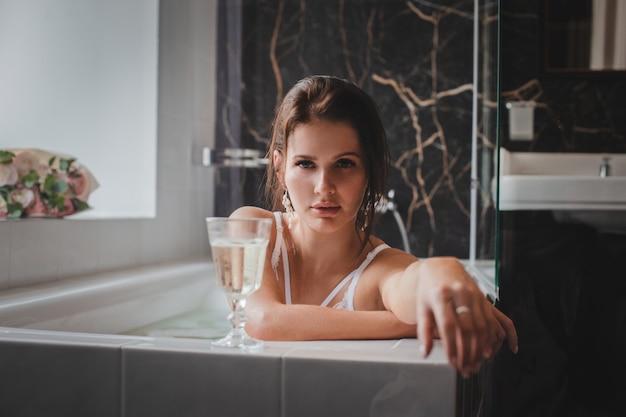 Ein junges schönes brünettes mädchen in weißer unterwäsche liegt mit einem glas champagner im badezimmer. morgen der braut im hotel im badezimmer.