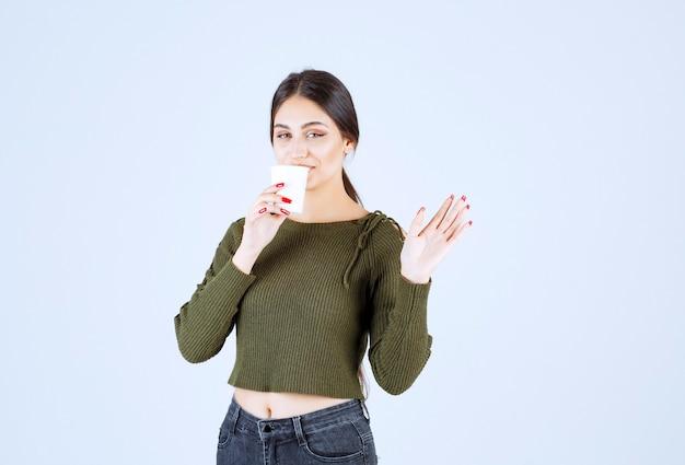 Ein junges schönes frauenmodell, das aus einem plastikbecher trinkt und eine hand winkt.
