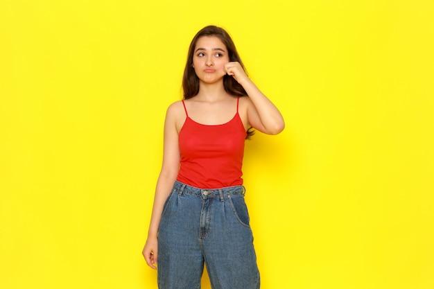 Ein junges schönes mädchen der vorderansicht im roten hemd und in den blauen jeans, die ihre wange abziehen