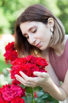 Ein junges schönes mädchen in einem sommerkleid nahe einem busch mit rosen im park.