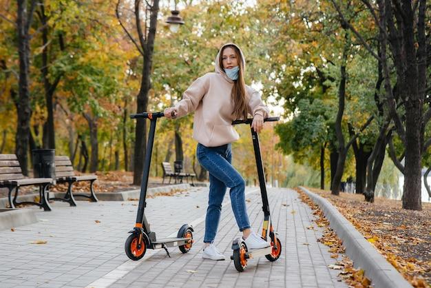 Ein junges schönes mädchen in einer maske fährt an einem warmen herbsttag mit einem elektroroller im park. im park spazieren gehen.