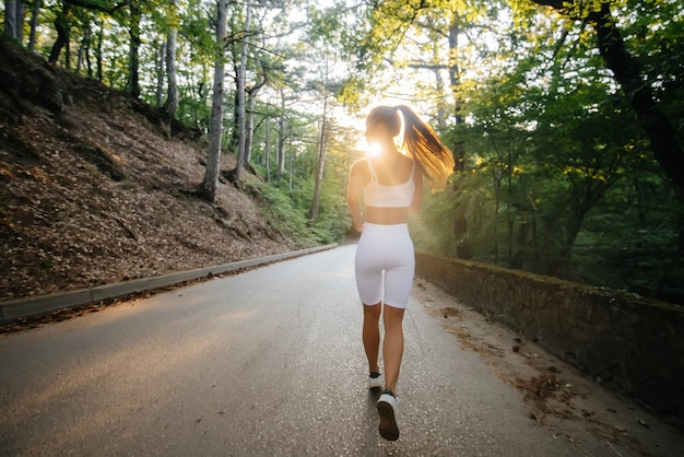 Ein junges schönes mädchen in weißer sportkleidung läuft während des sonnenuntergangs mit dem rücken auf der straße in einem dichten wald. sport an der frischen luft machen. eine gesunde lebensweise.