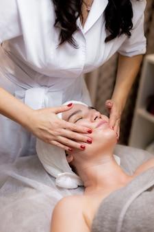 Ein junges schönes mädchen liegt auf dem tisch der kosmetikerin und erhält eingriffe, eine leichte gesichtsmassage.