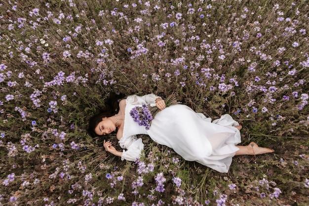 Ein junges schönes mädchen liegt mit geschlossenen augen in einem blühenden feld der provence. romantische atmosphäre
