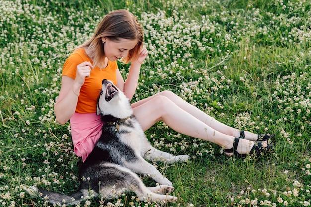 Ein junges schönes mädchen mit dem blonden haar sitzt auf der wiese mit ihrem haustierwelpenschlittenhund und scherzt.