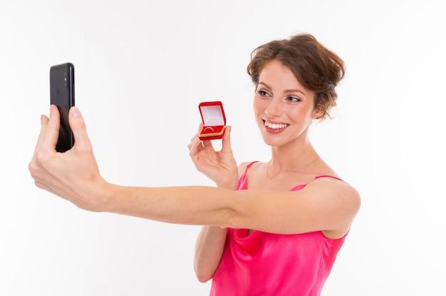 Ein junges schönes mädchen mit welligem braunem haar, sauberer haut, flachen zähnen, einem schönen lächeln in einem rosa trikot hält eine trainingsringbox und nimmt ein selfie mit