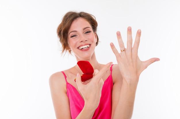 Ein junges schönes mädchen mit welligen braunen flecken, sauberer haut, flachen zähnen, einem schönen lächeln in einem rosa trikot hält eine trainingsringbox, zeigt den verlobungsring an ihrer hand und freut sich