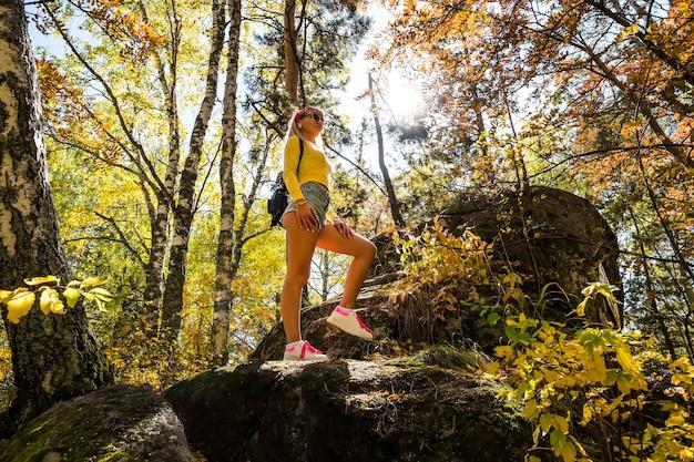 Ein junges schönes mädchen steht auf einem stein vor einem hintergrund von gelben blättern und birken. stilvolle frau im herbstwald.