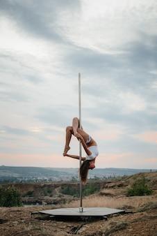 Ein junges sexy mädchen führt erstaunliche übungen auf einer stange während eines schönen sonnenuntergangs durch. tanzen. sexualität.