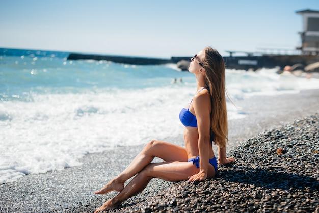 Ein junges sexy mädchen ruht sich an einem sonnigen tag auf dem meer aus. erholung, tourismus